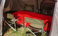 The interior of mess tent with dining chairs and table.